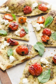 picture of crust  - Close up of gourmet thin crust pizza with roasted tomatoes - JPG
