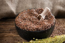 foto of flax seed oil  - Horizontal photo with stone marble mortar bowl full of flax seeds placed on wooden board with burlap in background - JPG