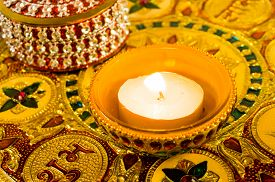 stock photo of diya  - Traditional diwali diya lamp lit and placed on a beautifully decorated and carved golden plate - JPG