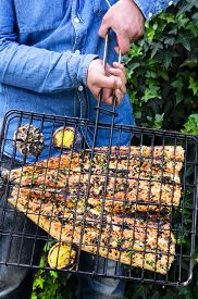 foto of baste  - Home chef showing his perfectly grilled fish fillet basted in lemon and herb butter at a barbeque barbecue bbq - JPG