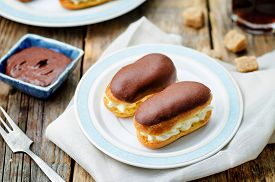 stock photo of eclairs  - eclairs with cheese cream and chocolate glaze on a dark wood background - JPG