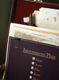 picture of nyse  - investment plan with planning process outlined in briefcase ready for review with stocks and planning paperwork behind the plan - JPG