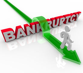 stock photo of debt free  - A man jumps over the word bankruptcy symbolizing freedom from debt - JPG