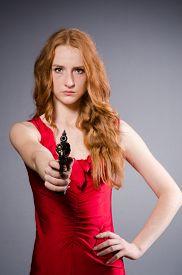 foto of handgun  - Girl in red dress with handgun against gray - JPG