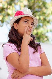 picture of ten years old  - Pensive child girl ten year old with a hat on the street - JPG