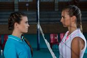 Aggressive female volleyball players looking each other through net at court poster