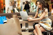 picture of internet-cafe  - Young lady browsing the Internet at the cafe - JPG