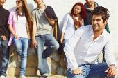group of teenagers standing against the wall with their leader in white shirt and jeans sitting infr