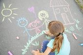 Child Draws A Family On The Pavement With Chalk. Selective Focus. poster