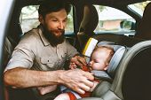 Father Putting Baby In Safety Car Seat Happy Family Vacation Road Trip Lifestyle Child Care Transpor poster