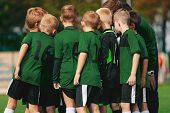 Group Of Young Boys In Green Jersey Shirts Standing With Coach On Soccer Field. Sports Team Putting  poster