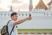 Asian Blogger Man Travel In Bangkok, Thailand, Backpacker Male Using Mobile Phone Make Vlog And Live poster