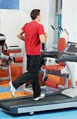 smiling fitness man at legs muscles exercises with running training machine station in gym