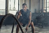 Strong young man working out with battle ropes in a crossfit gym. Muscular sportsman doing cross exc poster
