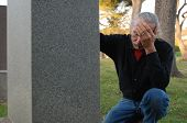 stock photo of bereavement  - Man sitting at gravesite with his head in his hands - JPG