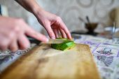 Girl Cuts Avocado On The Board. Girl Cuts Green Ripe Avocado With Knife. Fruit Is Cut On Wooden Cutt poster