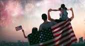 Patriotic holiday. Happy family, parents and daughter child girl with American flag outdoors. USA ce poster