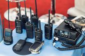 Many Portable Radio Transceivers On Table At Technology Exhibition. Different Walkie-talkie Radio Se poster