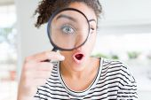 Young african american woman looking through magnifying glass scared in shock with a surprise face,  poster