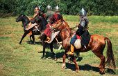 Group Of Ancient Equestrians In Historical Costumes Are Reconstructed. The Medieval Armored Knights  poster