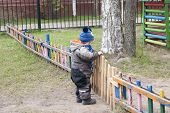 A Small Boy Of Three Years Old On A Cool Spring Sunny Day Is Trying To Open A Small Wooden Fence To  poster