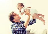 family, fatherhood and parenthood concept - happy smiling young father with little baby at home poster