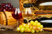 Wooden case with wine bottles, barrel, wineglass and grape on wooden table on grey background