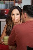 stock photo of sulky  - Doubtful woman looking at man sitting in cafe - JPG