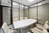 picture of louvers  - Light office blinds closed with a table and leather chairs - JPG