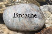 stock photo of oxygen  - Positive reinforcement word Breathe engrained in a rock - JPG