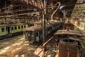 stock photo of railroad yard  - Cargo trains in old train depot left to be eaten by the rust - JPG