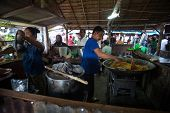 PADANG - AUGUST 25: Food hawkers prepare rice dishes at their stall at a village market in Padang, S