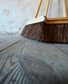 stock photo of sweeper  - Close up large brooms for house work on old wooden floor of country house - JPG
