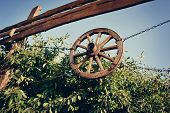 stock photo of covered wagon  - on the fence on chains hanging wooden wagon wheel - JPG