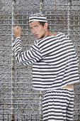 image of prison uniform  - Portrait of young male prisoner in uniform standing against prison cell - JPG