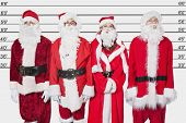stock photo of lineup  - People in Santa costume standing side by side against police lineup - JPG