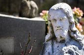 stock photo of headstones  - statue of jesus in front of a headstone in a graveyard - JPG