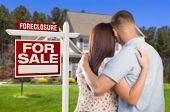 stock photo of possession  - Military Couple in Front of House and Foreclosure For Sale Real Estate Sign - JPG
