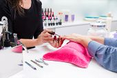 Nail saloon woman painting color nail polish in hands over pillow with pink towel