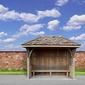 stock photo of bus-shelter  - An Old Wooden Bus Shelter with Red Brick Wall and Blue Sky - JPG
