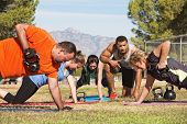 stock photo of kettlebell  - Male instructor training mature adults in boot camp fitness - JPG