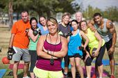 stock photo of middle class  - Smiling confident trainer standing with fitness class - JPG