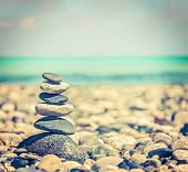 Vintage retro hipster style travel image of Zen meditation background -  balanced stones stack close
