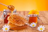 stock photo of pot gold  - Honey in jar with honeycomb and wooden drizzler - JPG