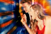 stock photo of arcade  - Gambling couple in Casino or amusement arcade on slot machine winning - JPG