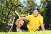 Mature man in sportswear sitting on grass near his bicycle in a park