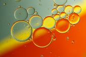 foto of drop oil  - Oil drops on a water surface with color background - JPG