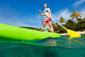 stock photo of paddling  - Mother and her adorable little daughter paddling on stand up board having fun during summer beach vacation - JPG
