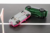 pic of deformed  - two turned toy cars on the road [[** Note: Soft Focus at 100%, best at smaller sizes] ** Note: Visible grain at 100%, best at smaller sizes - JPG