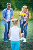 image of frisbee  - Parents playing frisbee with their daughter - JPG